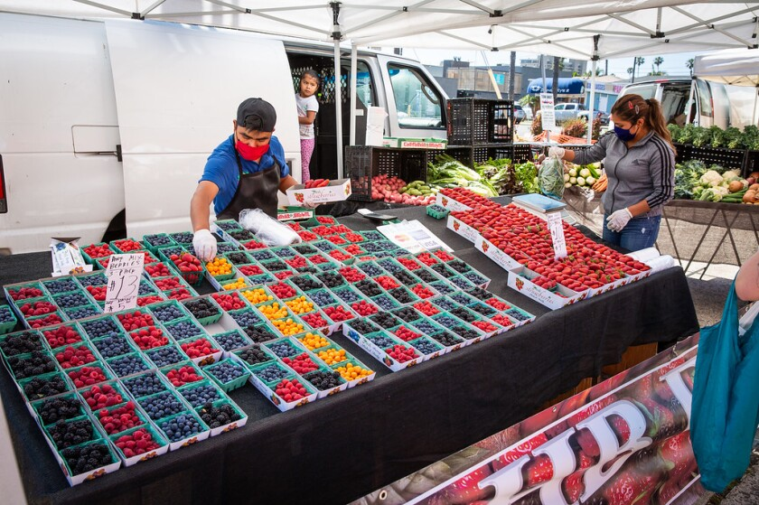 XXXX Family Farm of San Luis Obispo County sets out its collection of produce for Pacific Beach's Garnet Avenue farmers market, which returned May 19 after being closed because of coronavirus restrictions.