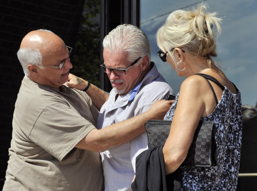 """Steven Davis, center, brother of slain Debra Davis, is comforted by Skip Marcella after speaking outside federal court in Boston where a jury found James """"Whitey"""" Bulger guilty on several counts of murder, racketeering and conspiracy. Jurors could not agree whether Bulger was involved in Davis' killing. Family members are hoping they will be allowed to speak during Bulger's sentencing hearing."""