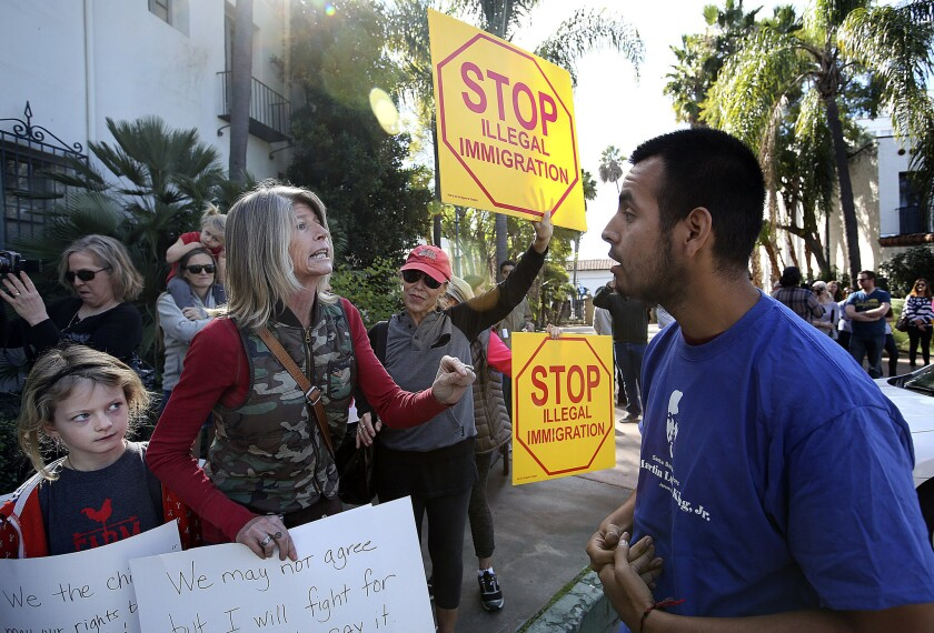Mona Hansen, who supports the Santa Barbara News-Press, argues with Julio Ricon.