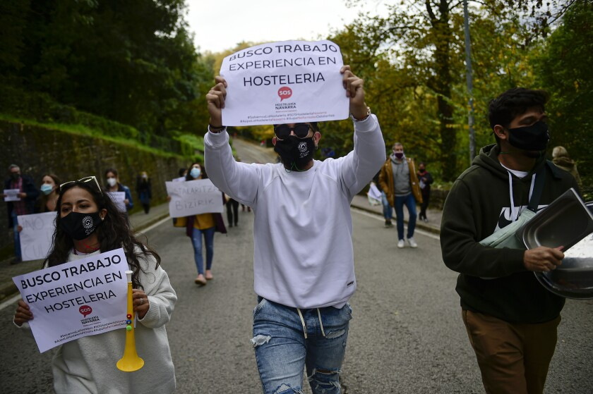 People hold up banners in support of the hotel industry in Pamplona, northern Spain.