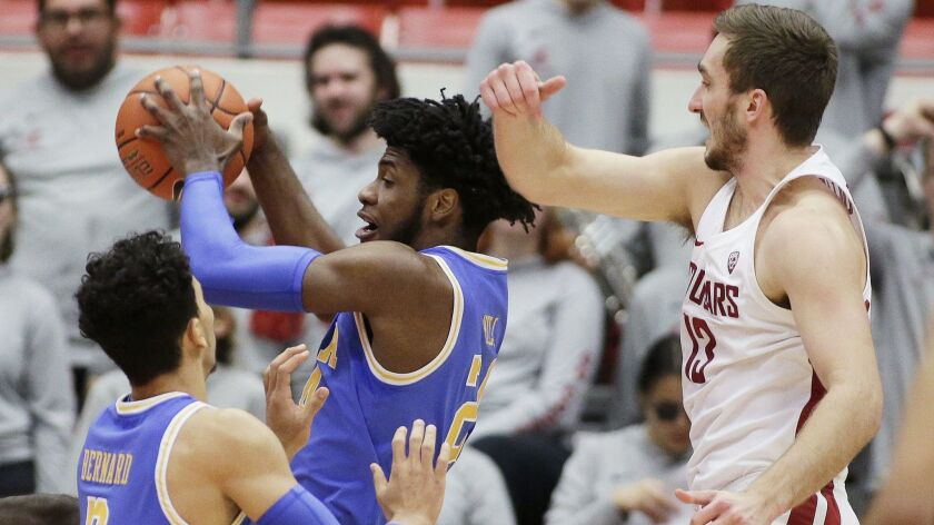 UCLA guard Jalen Hill, center, grabs a rebound in front of guard Jules Bernard, left, and Washington
