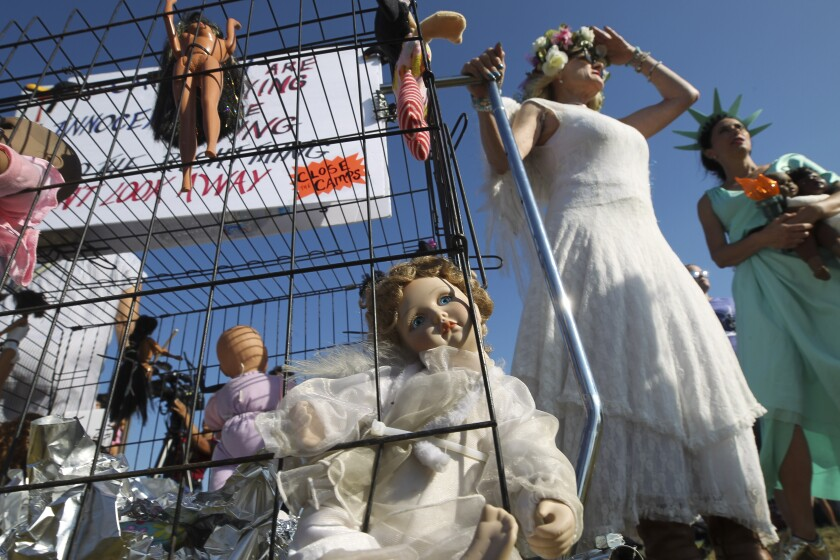 Tarra Lynne, dressed as an angel, and Alisa Davies, wearing a Statue of Liberty costume, stand next to a cage with dolls inside to represent detained migrant babies and mothers, made by Lynne, during a protest rally demanding the closure of migrant detention camps on Friday in San Ysidro.
