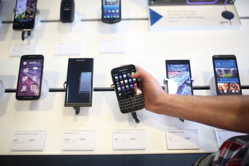 Un empleado de una tienda de teléfonos muestra un modelo de BlackBerry.