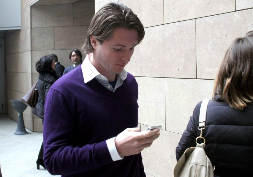 """Raffaele Sollecito checks his smart phone as he enters the Florence court, Italy, Thursday, Jan. 9, 2013. The defense lawyer for the former boyfriend of U.S. exchange student Amanda Knox told an appeals court Thursday that the young lovers were blamed by authorities for the murder of British student Meredith Kercher to calm any fears that a monster was loose in their Italian university town. Defender Giulia Bongiorno said her client, Raffaele Sollecito, and Knox were identified as suspects in a """"record"""" four days after the murder in the picturesque central town of Perugia because authorities """"did not want to think that a stranger, a monster, could have entered a house and murdered a student."""" (AP Photo/Matteo Bovo, Lapresse)"""