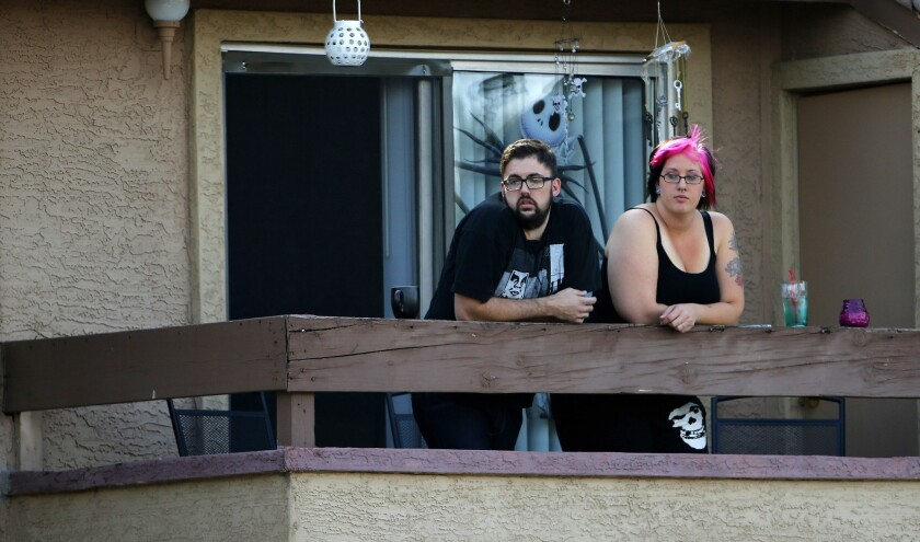 Neighbors watch as authorities search an apartment in North Phoenix believed to be the home of two gunmen who were fatally shot at the Garland, Texas, center hosting the exhibit and Muhammad cartoon contest.