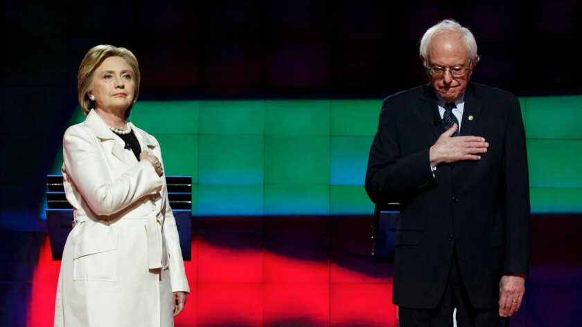 Hillary Clinton and Bernie Sanders standing during the National Anthem at the start of a debate at the Brooklyn Navy Yard in Brooklyn, New York on April 14.