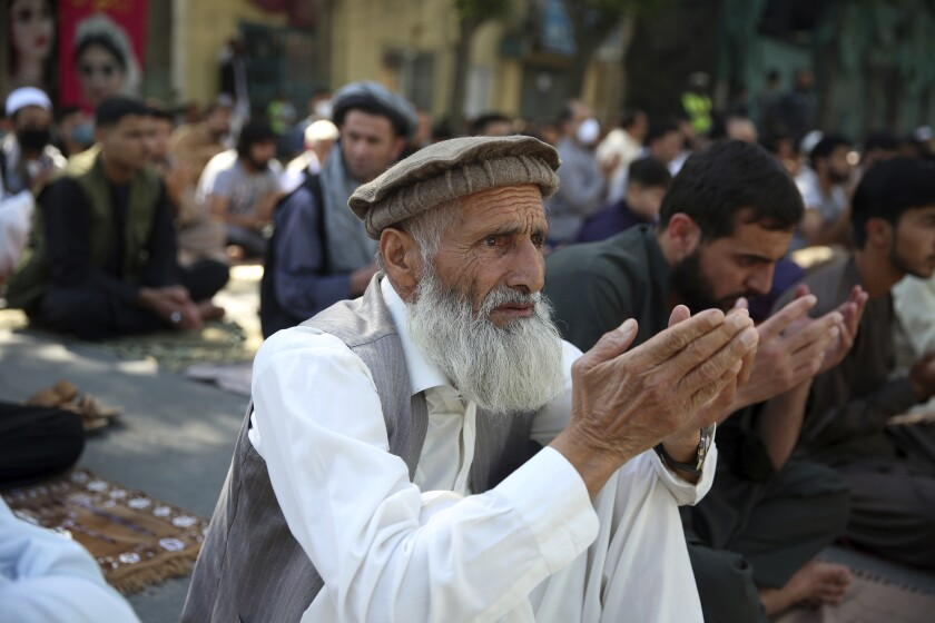 Men pray outside a mosque in Kabul, Afghanistan