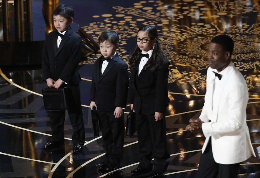 Oscars host Chris Rock, right, introduces three Asian children as Price Waterhouse representatives during a controversial spoof at the 88th Academy Awards.