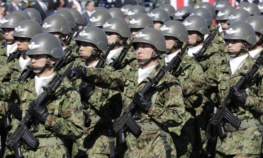 FILE - In this Oct. 27, 2013 file photo, members of Japan Self-Defense Forces march during the Self-Defense Forces Day at Asaka Base, north of Tokyo. Japan's annual defense white paper approved by the Cabinet on Tuesday, Aug. 5, 2014, expresses strong concern about China's military build-up, citing its neighbor's increased airspace and maritime activities. But officials said separately that Japan's defense budget may be insufficient to achieve the goals set by Prime Minister Shinzo Abe to bolster the country's military. (AP Photo/Shizuo Kambayashi, File)