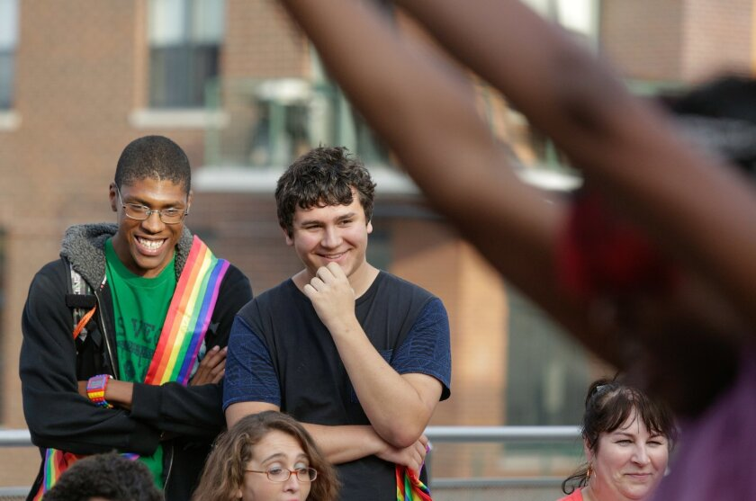In this Wednesday, June 17, 2015 photo, Jasean Purdis, left, laughs with Boy Scout David Fite as David judges a dance competition at a Gay Pride party for youth at the Center on Halsted in Chicago. Among other projects, David, hosted the party to support the city's gay community and earn his Eagle