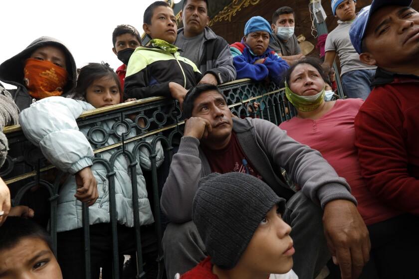 Men, women and children along a railing.