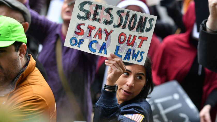 Anoosh Jorjorian holds up a sign as protesters rally outside a hotel where Atty. Gen. Jeff Sessions was speaking in Sacramento.
