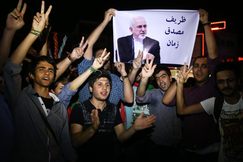 """FILE -- In this July 14, 2015 file photo, young Iranian men cheer and show victory signs while holding a picture of Foreign Minister Mohammad Javad Zarif, reading """"Zarif is Mosaddegh of our time,"""" comparing Zarif to Mohammad Mosaddegh, Iran's legendary prime minister during the 1950s who nationaliz"""