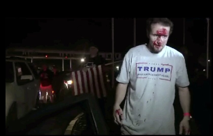 This still image taken from video shows a supporter of Republican presidential candidate Donald Trump after a protest on Thursday, April 28, 2016 in Costa Mesa, Calif.  Dozens of protesters were mostly peaceful Thursday as Trump gave his speech inside the Pacific Amphitheater. After the event, howe