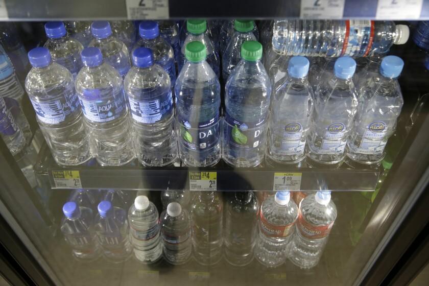 Varieties of bottled water in a refrigerator.