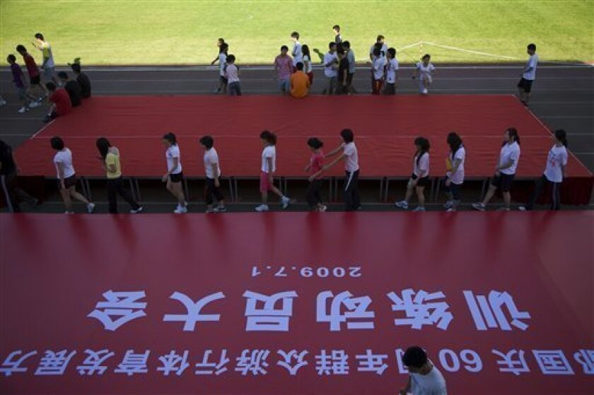 Students at the Capital Institute of Physical Education walk past a backdrop prepared for a ceremony marking the mobilization of personnel for the 60th National Day celebrations at the school's field in Beijing, China, Wednesday, July 1, 2009. As the government gears up for a lavish celebration to mark Communist China's 60th anniversary on Oct. 1, indignation is being voiced by many students across the city who are unhappy about having to sacrifice their summer holidays to prepare for the event. (AP Photo/Ng Han Guan)