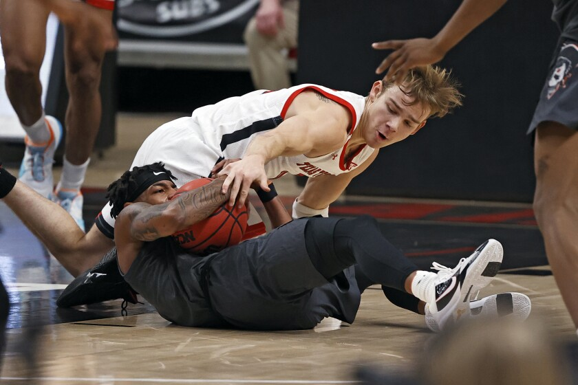 Oklahoma State's Avery Anderson III, bottom, and Texas Tech's Mac McClung, top, fight for the ball during the first half of an NCAA college basketball game Saturday, Jan. 2, 2021, in Lubbock, Texas. (AP Photo/Brad Tollefson)