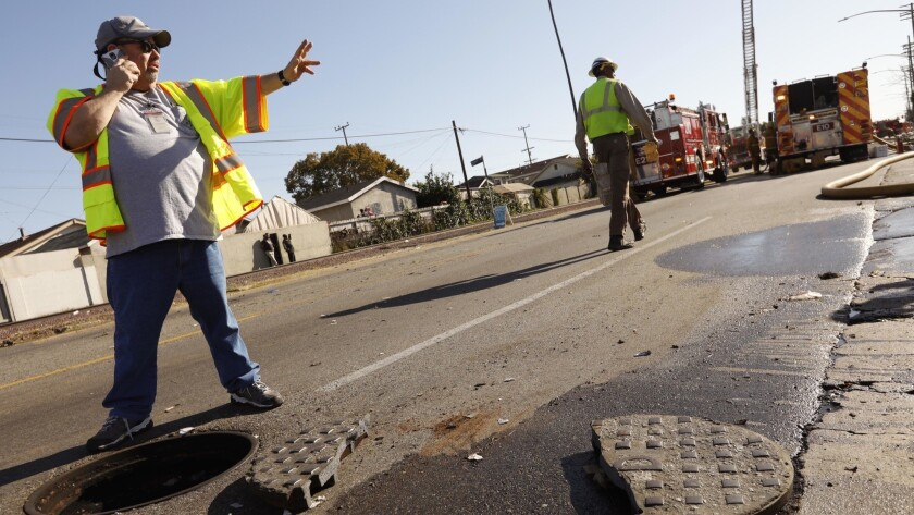 Dan Rodriguez, a supervisor with the Los Angeles Sanitation Department, stands near a manhole cover that was sheared in two.