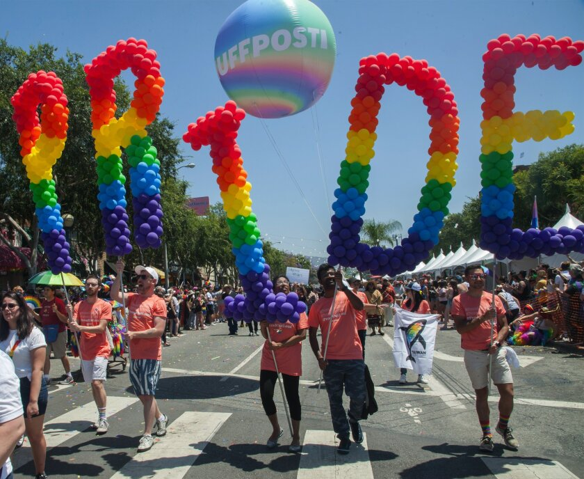 """Marchers in the 2019 LA Pride parade carry multicolored balloons spelling out """"Pride"""" in West Hollywood."""