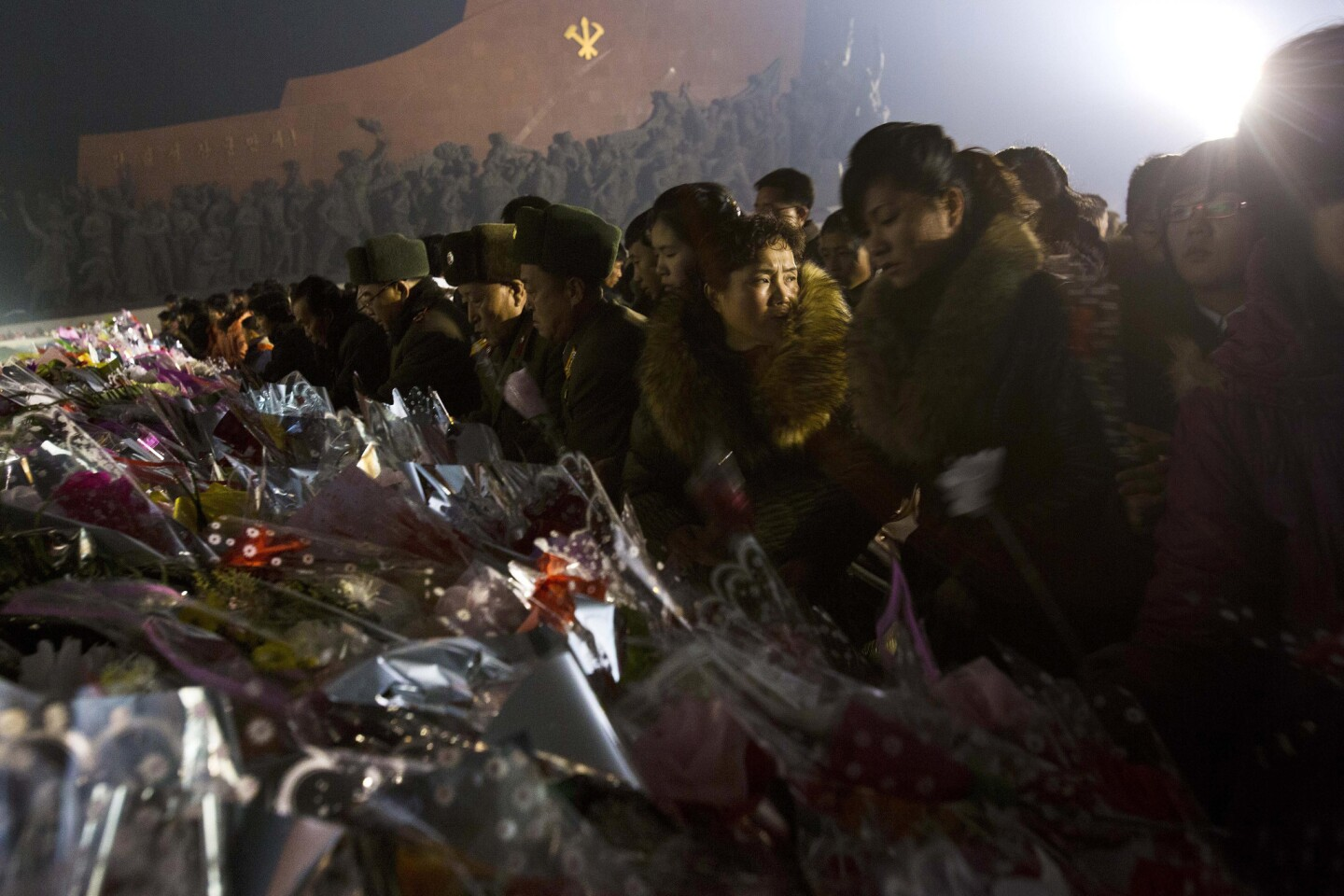 North Koreans lay flowers at the base of statues of the nation's founder, Kim Il Sung, and late leader Kim Jong Il in Pyongyang in December 2013 to commemorate the second anniversary of Kim Jong Il's death.
