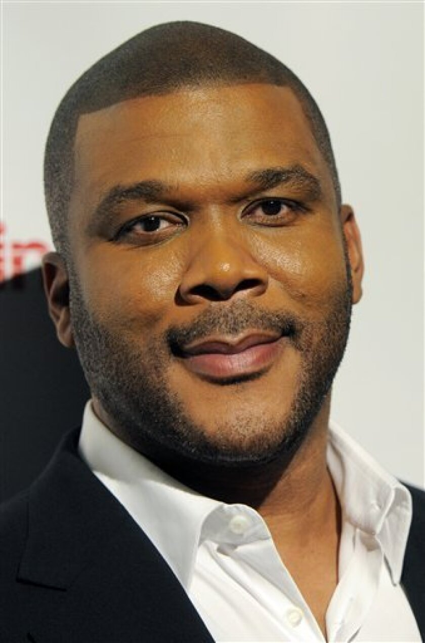 FILE - In this March 31, 2011 file photo, Tyler Perry, recipient of the CinemaCon Visionary Award, arrives for the CinemaCon Big Screen Achievement Awards in Las Vegas. Perry delivered on a Christmas promise when he handed the keys of a new four-bedroom house to an 88-year-old woman who lost her rural Georgia home to a fire. (AP Photo/Chris Pizzello, File)