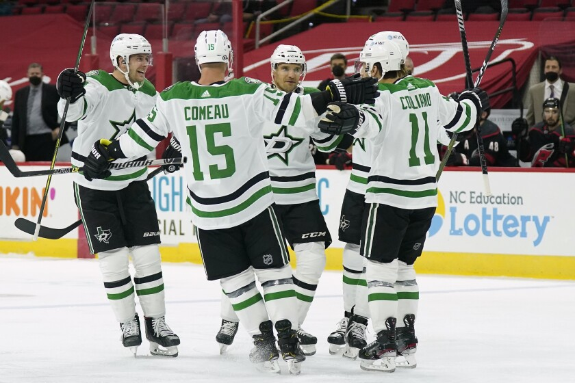 Dallas Stars defenseman Mark Pysyk, left, celebrates his goal against the Carolina Hurricanes with left wing Blake Comeau (15), center Andrew Cogliano (11) and defenseman Andrej Sekera, center, of Slovakia, during the first period of an NHL hockey game in Raleigh, N.C., Saturday, April 3, 2021. (AP Photo/Gerry Broome)