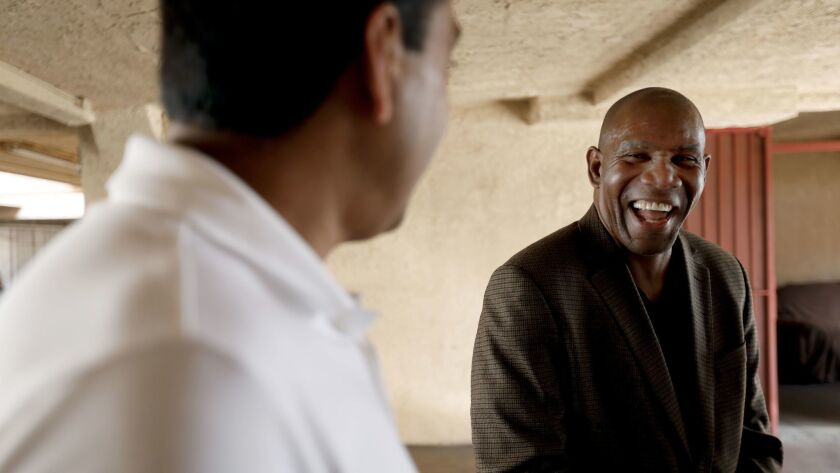 Motel owner Joe Patel, left, talks with Rev. Richard Reed, right, Executive Director of the nonprof