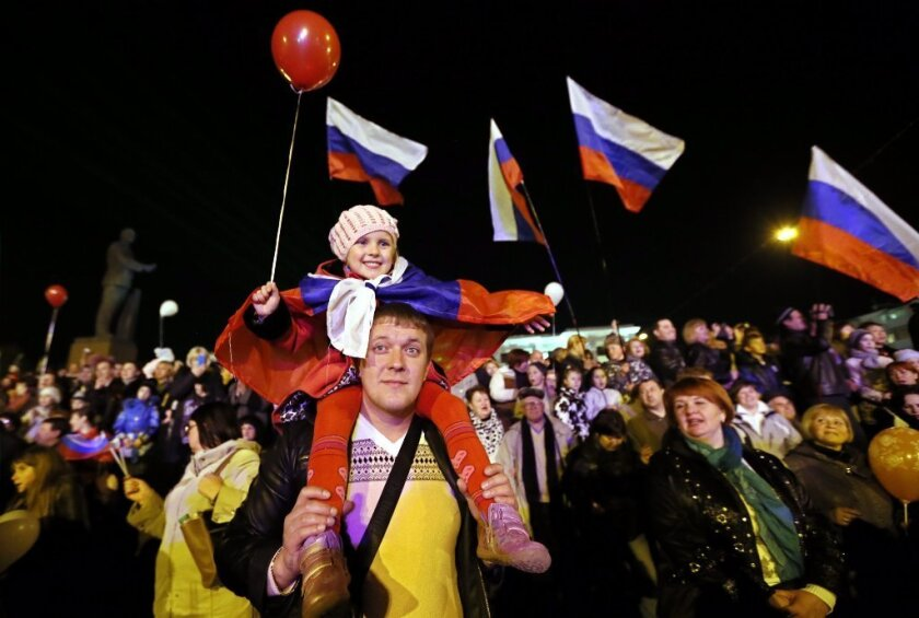 Crimeans celebrate in the central square in Simferopol, Ukraine on Friday. Russian President Vladimir signed a bill Friday making Crimea and the city of Sevastopol part of Russia.