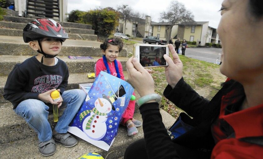 Volunteer Jessica Yang takes a photo of recently arrived Syrian refugee siblings Majerid, 7, left, and Jory, 4, outside their family's new apartment in Dallas. Texas officials have sought a court order blocking further Syrian resettlement.