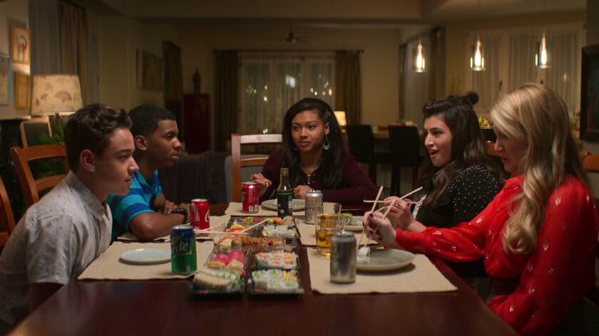 A group of teenagers sits around a dining table eating sushi.
