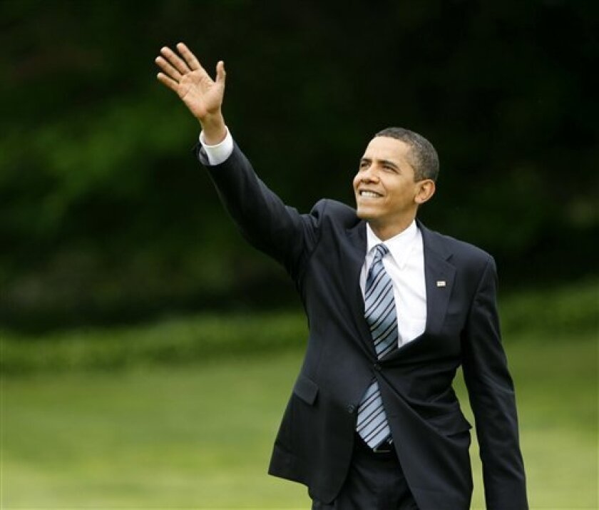 President Barack Obama waves to his daughter Sasha who was on the Truman Balcony as he arrives on the South Lawn of the White House in Washington, Thursday, May 14, 2009. (AP Photo/Gerald Herbert)