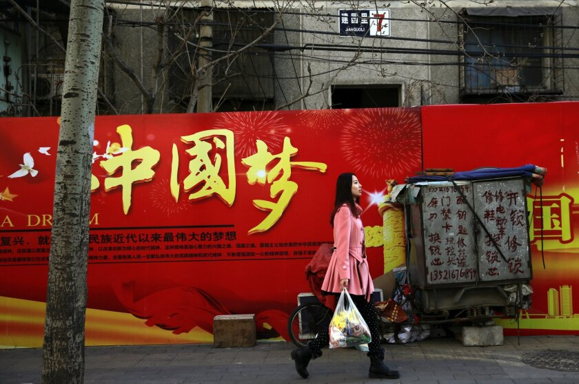 """A woman carries a bag of groceries as she walks past a Chinese government billboard stating """"China Dream"""" near a residential building in Beijing, on Thursday, Feb. 26, 2015. Since taking the reins of the ruling Communist Party in 2012, President Xi Jinping has leveraged slogans to promote his program of strengthening party rule, cracking down on corruption and building up China's international standing. The most famous of these has been the Chinese Dream, a fuzzy concept that seeks to motivate the nation's 1.3 billion people to realize prosperity, happiness and their rightful place on the world stage. (AP Photo/Andy Wong)"""