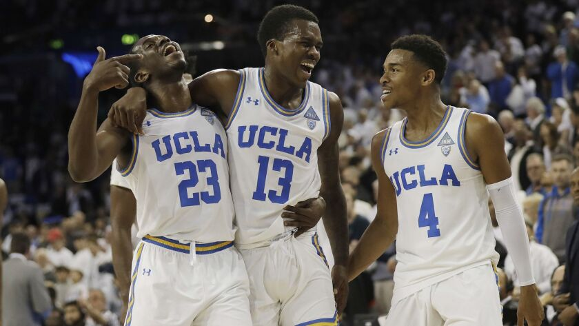 UCLA guard Kris Wilkes (13) celebrates after scoring the go-ahead basket with teammates Prince Ali (23) and Jaylen Hands (4) against Notre Dame.
