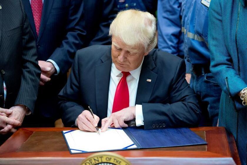 El presidente de los Estados Unidos, Donald J. Trump (c), firma la Resolución H.J. 38, desaprobando la regla presentada por el Departamento del Interior de los Estados Unidos conocida como la Regla de Protección de Flujo, hoy, jueves 16 de febrero de 2017, en la Sala Roosevelt de la Casa Blanca en Washington, DC, (EE.UU.). EFE/POOL