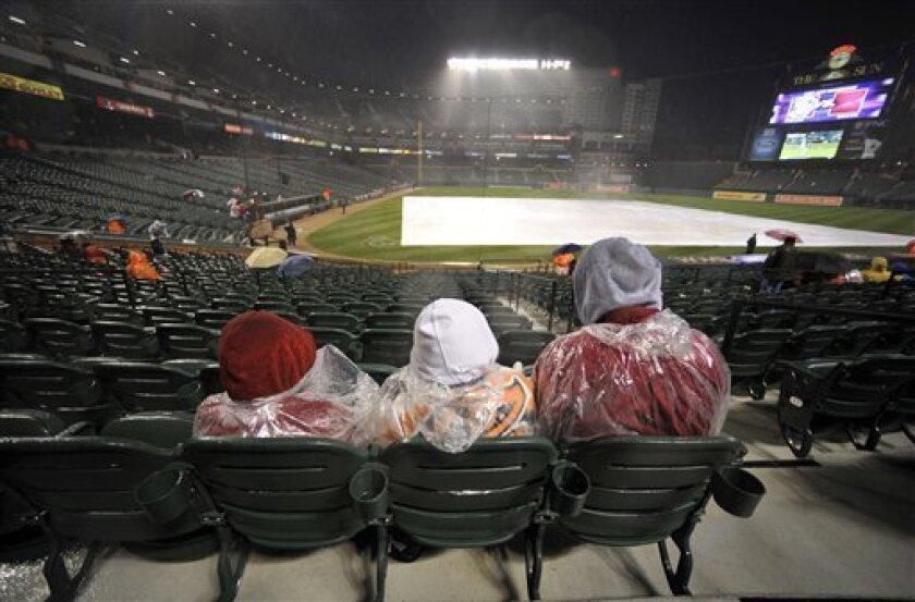 Baseball fans sit in the rain during a delay before the Baltimore Orioles against the Texas Rangers baseball game on Friday, April 8, 2011, in Baltimore.(AP Photo/Gail Burton)