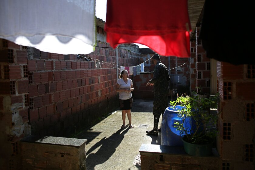 An army soldier visit talks to a woman at a home during an operation to eradicate Aedes aegypti mosquito breeding sites, in the Brazlandia neighborhood of Brasilia, Brazil, Wednesday, Feb. 17, 2016. The Aedes aegypti mosquito is a vector for the spread of the Zika virus and it lives largely inside