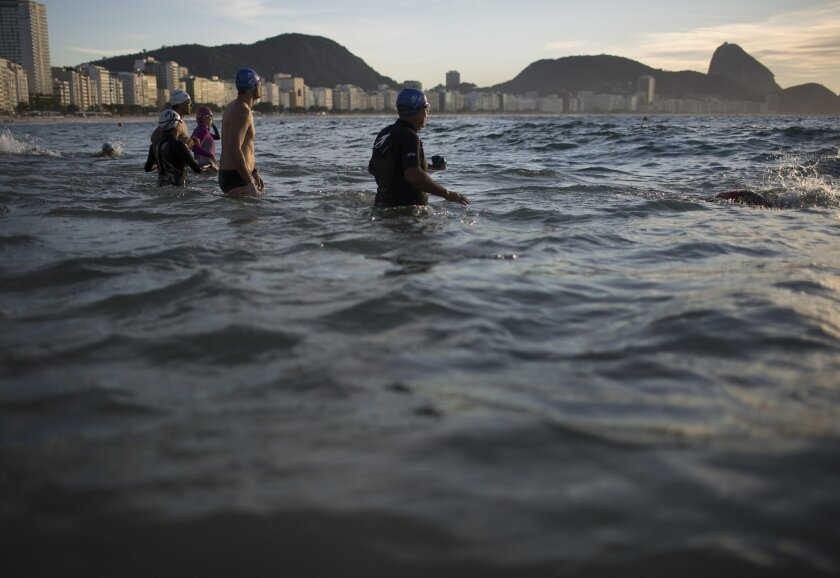 In this July 14, 2015 photo, beachgoers wade into the waters of Copacabana Beach in Rio de Janeiro, Brazil. An Associated Press analysis of water quality found not one water venue safe for swimming or boating in Rio's waters. Over 10,000 athletes from 205 countries are expected to compete in next year's Summer Olympics. Hundreds of them will be sailing in the waters near Marina da Gloria in Guanabara Bay; swimming off Copacabana Beach; and canoeing and rowing on the brackish waters of the Rodrigo de Freitas Lake. (AP Photo/Leo Correa)