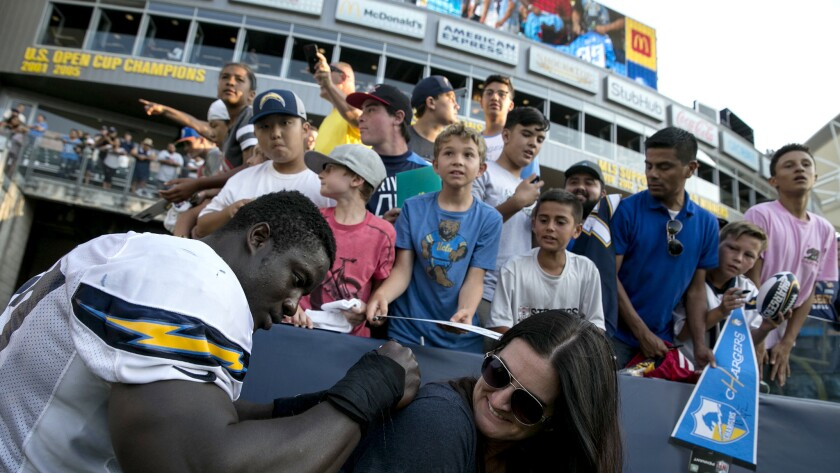 Chargers defensive end Jeremiah Attaochu autographs the shirt of fan Carrie O'Leary following a joint practice with the Rams on Saturday at StubHub Center.