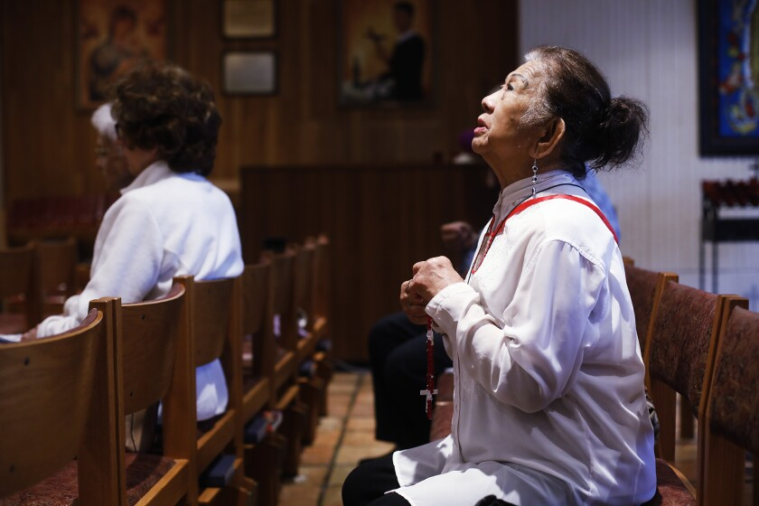 Esther Gianan, of Tampa, a retired registered nurse, prays for those who are affected by the coronavirus during Mass at St. Lawrence Catholic Church in Tampa, Fla., Friday, March 6, 2020. (Octavio Jones/Tampa Bay Times via AP)