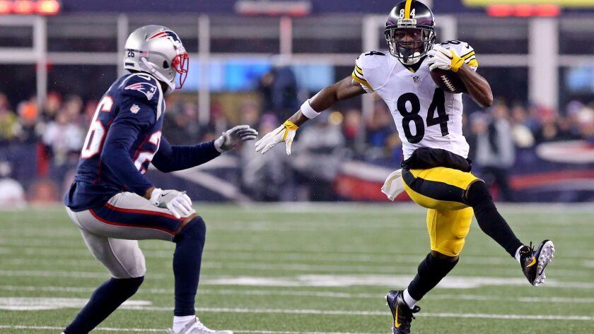 Jan 22, 2017; Foxborough, MA, USA; Pittsburgh Steelers wide receiver Antonio Brown (84) runs the ball against New England Patriots cornerback Logan Ryan (26)