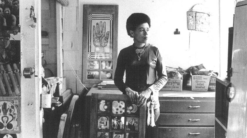 "Portrait of Betye Saar in her Laurel Canyon Studio, 1970. Standing with ""Black Girl's Window,"" 1969, which was acquired by MOMA in 2013."