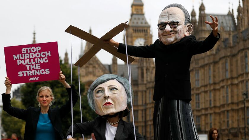 Campaigners from the community-based organization Avaaz, wearing a mask of Rupert Murdoch, right, an