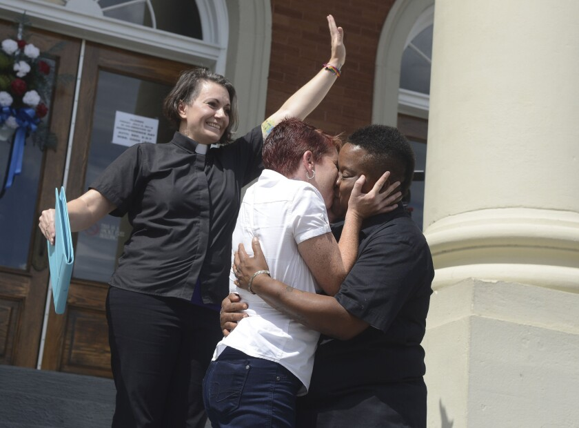 Amber Hamilton and Annice Smith share their first kiss as a married couple in front of by Pastor Brandiilyne Dear on the steps of the Forrest County Courthouse in Hattiesburg, Miss.