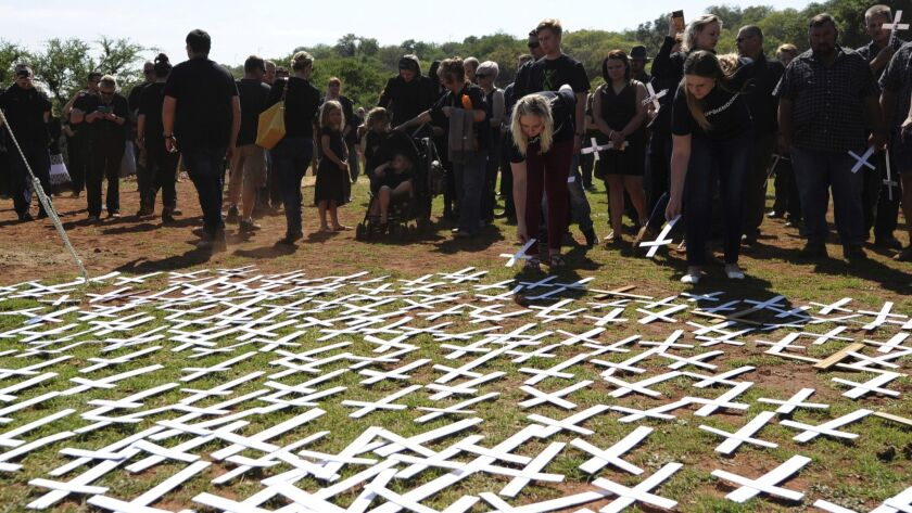 In this photo taken Oct. 30, 2017 people place white crosses, representing farmers killed in the cou