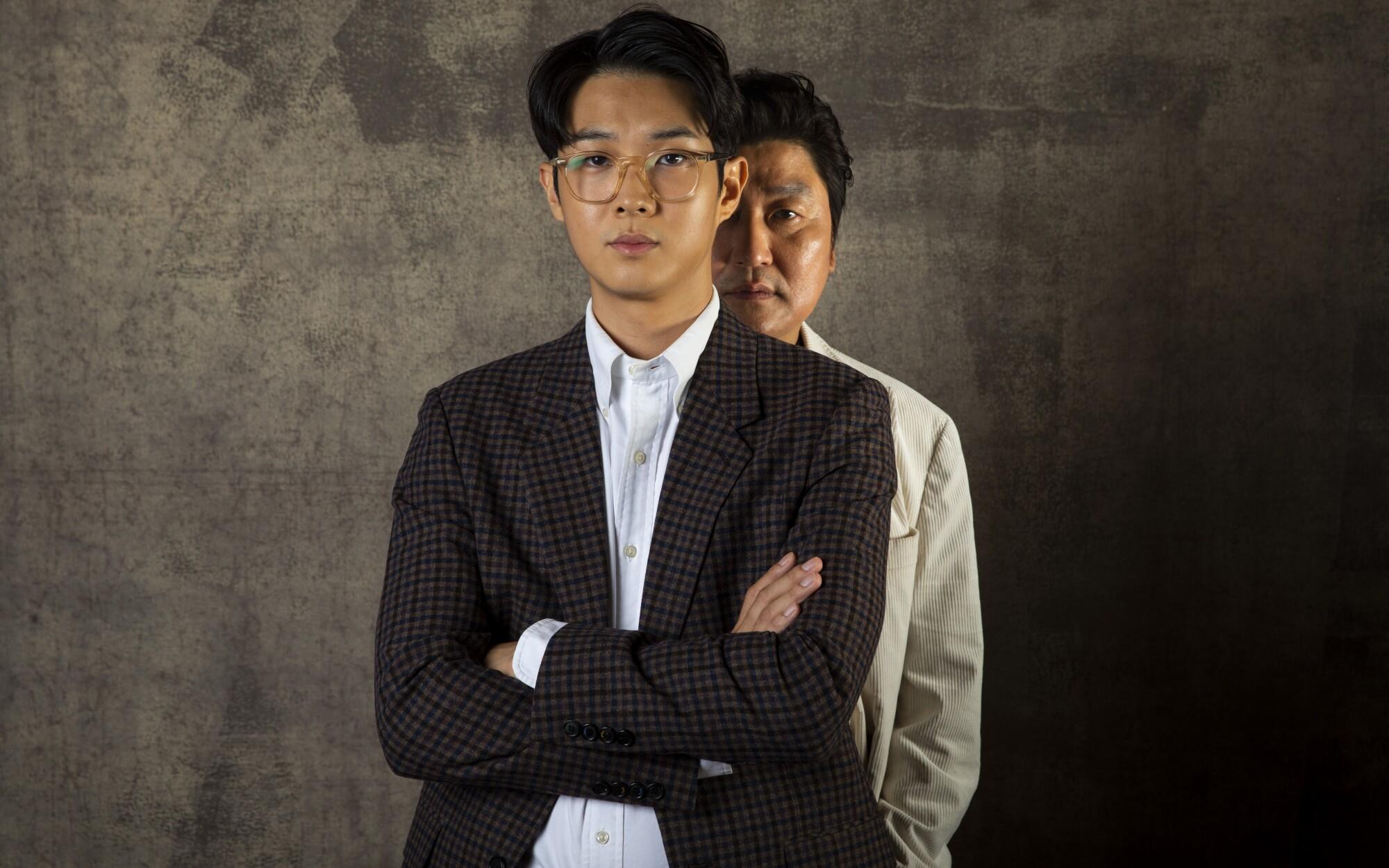 Choi Woo Shik with Song Kang Ho standing behind him