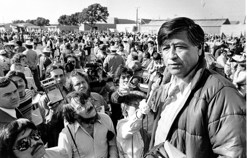Cesar Chavez stands surrounded by reporters.