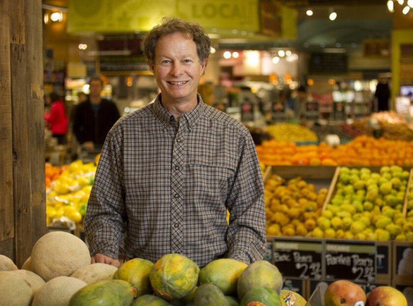John Mackey, CEO of Whole Foods, in the produce section of a market.