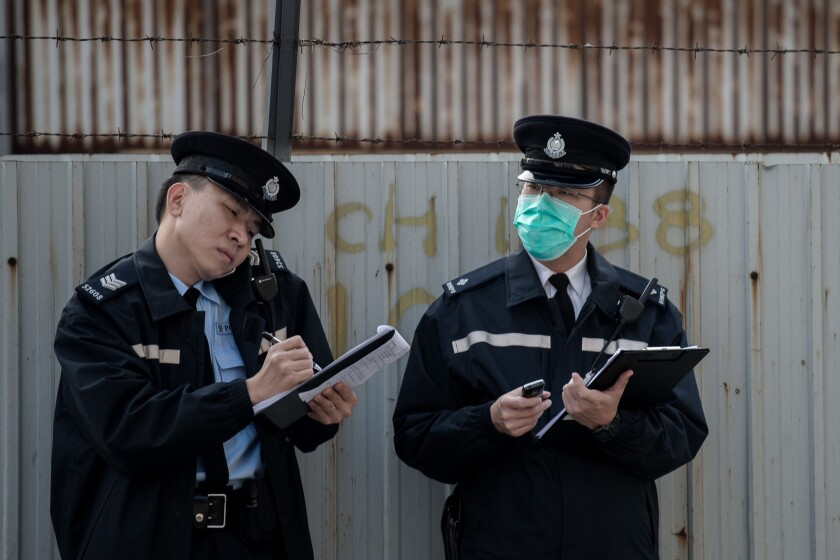 Two policemen take notes Jan. 28, 2014, near a wholesale market where infected poultry imported from mainland China was discovered in Hong Kong. Hong Kong is among the places that have been affected by the H7N9 bird flu virus, which has been less deadly than the SARS epidemic.