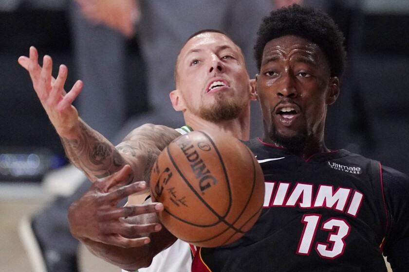 Miami Heat's Bam Adebayo (13) is tied up by Boston Celtics' Daniel Theis, background, during the second half of an NBA conference final playoff basketball game Sunday, Sept. 27, 2020, in Lake Buena Vista, Fla. Adebayo was fouled on the play. (AP Photo/Mark J. Terrill)