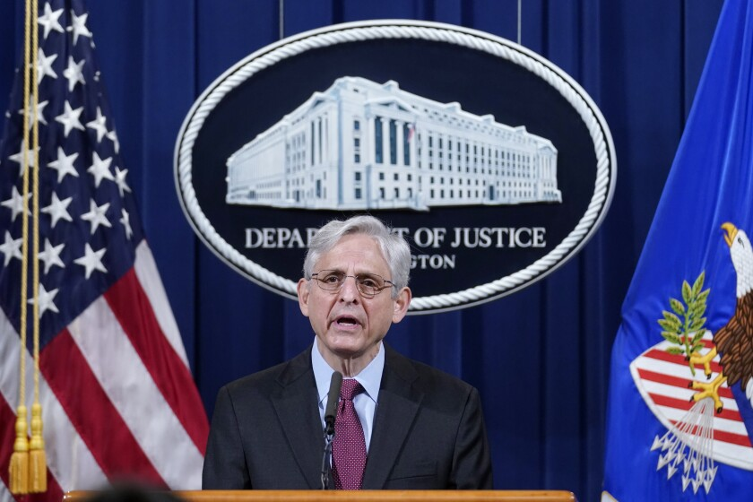 """Merrick Garland speaks at a podium, a """"Department of Justice"""" sign and flags behind him."""